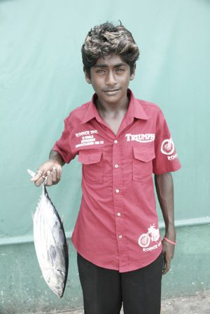Maldivain boy with fish at market.jpg